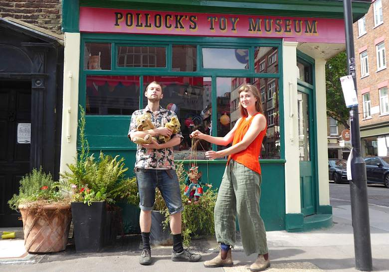 Jack Fawdry holding two teddy bears, and Emily Baker pulls the strings of a toy theatre puppet outside the Toy Museum.