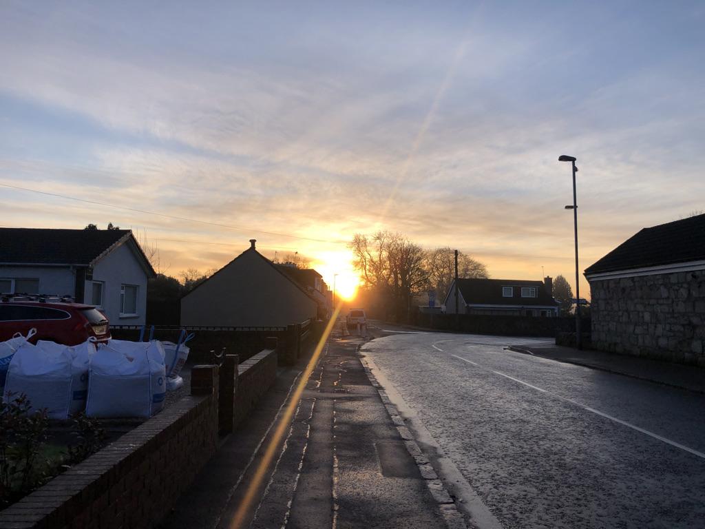Main street Chryson with sun rising behind houses.