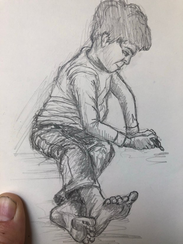 Drawing of boy coloring on a table.