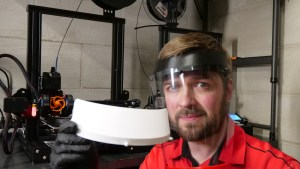 """Josh holds a face shield headband in the original """"factory"""" - his basement!"""