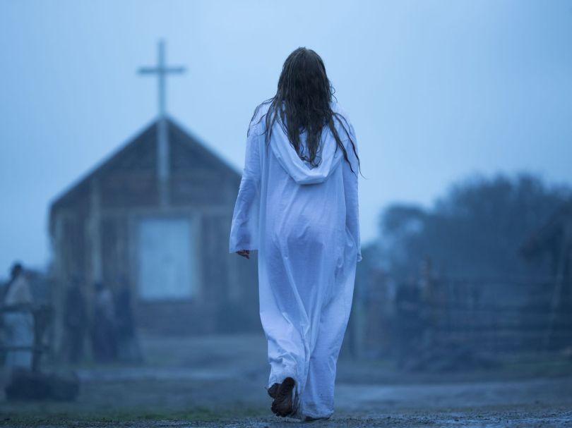 A woman in a white robe walks toward a church.