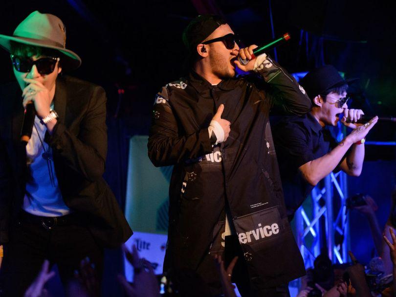 Epik High's DJ Tukutz, Mithra Jin, and Tablo hold mics and sing on stage.