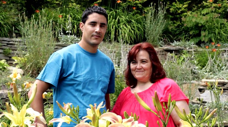 A young man and a middle-aged woman stand in a garden.