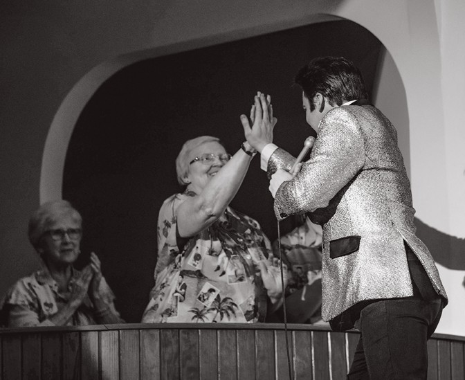 Dwight Icenhower reaching out to touch his hand against a woman's during a performance