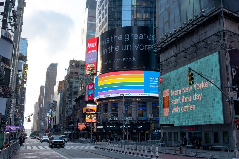 The curved video screen over the entrance to a Chase Bank building in New York City displays a rainbow flag for Pride month.