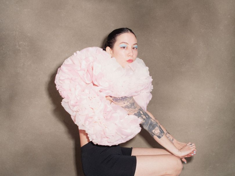 Michelle Zauner, the musical artist known as Japanese Breakfast, sits in a puffy pink top and looks directly at the camera.