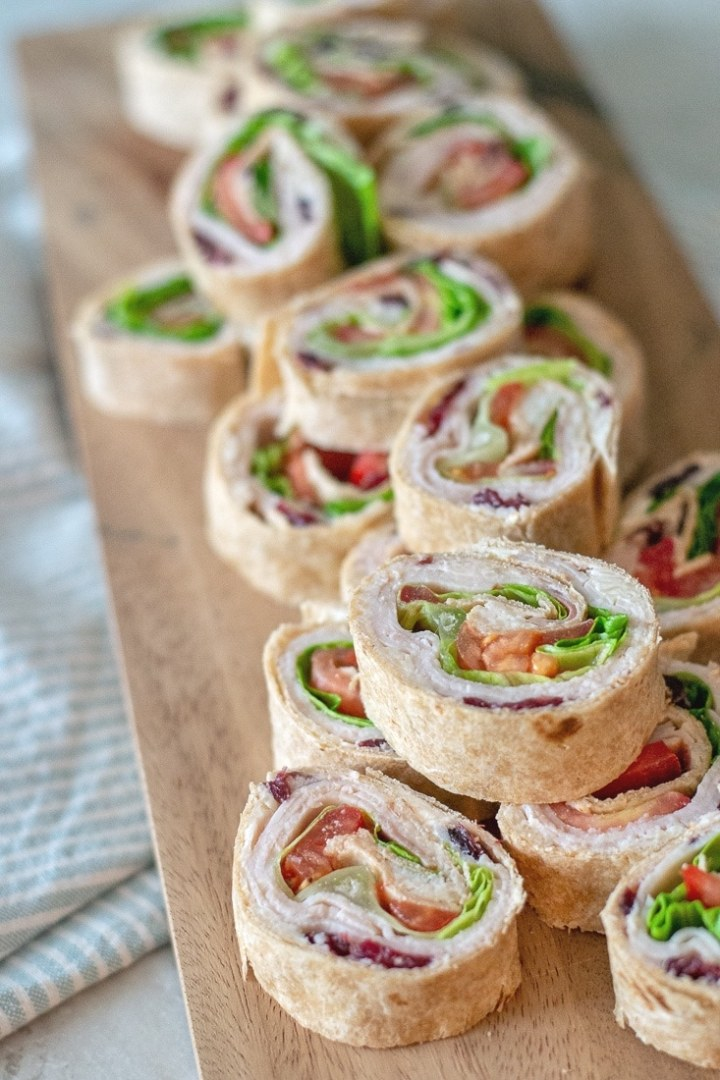 Cranberry Turkey Pinwheels make an awesome cold appetizer for Thanksgiving or even a great, healthier no heat lunch. These are made with a cream cheese, swiss and cranberry spread that makes these extra delicious!