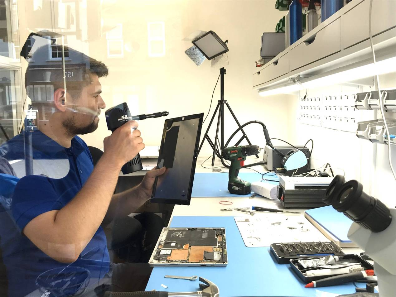 Daniel is making sure that the new screen he is going to fit, has the camera lens clean from both sides of the replacement part of the surface pro 3