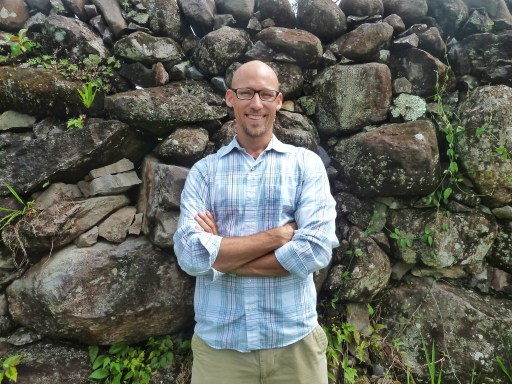 Adam standing in front of a stone wall, smiling