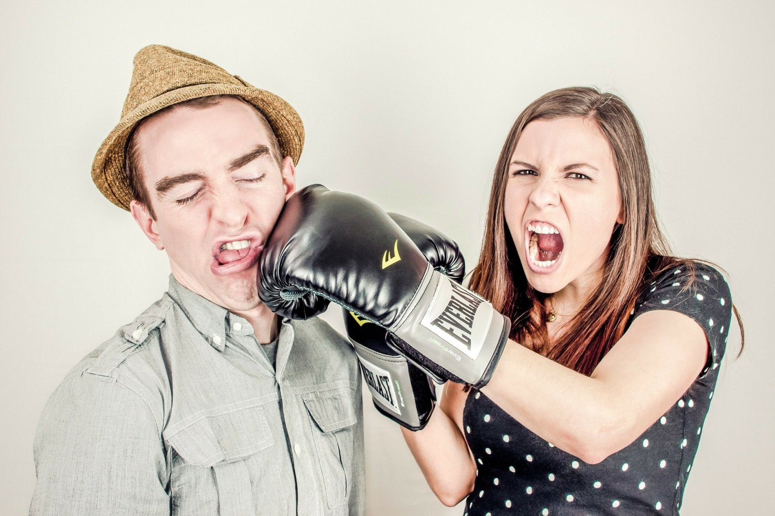 Screaming woman with boxing gloves, punching a man in the face, fighting in a relationship