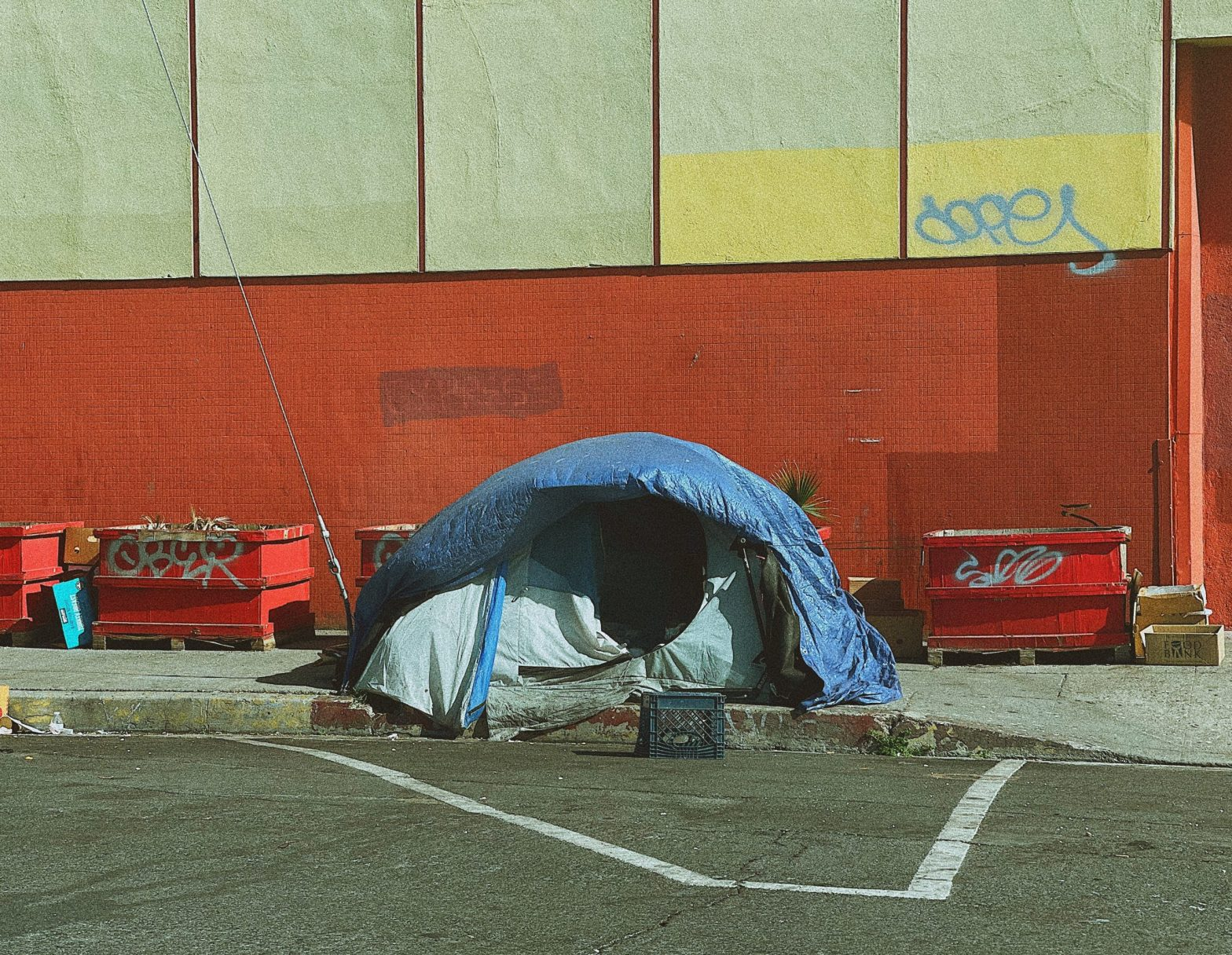 Tent on the sidewalk by some dumpsters. Survival vs living.