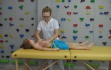 Masaż leczniczy dziecka leżącego na stole rehabilitacyjnym