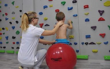rehabilitacja dziecka wykonującego ćwiczenia fizjoterapetyczne na piłce