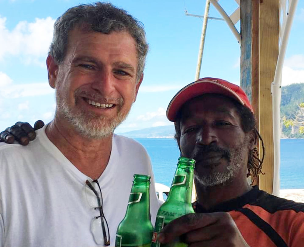 The picture at the center of a controversial television commercial produced by Milissa Holland's campaign, showing candidate Alan Lowe, left, and Philip, a resident of Dominica, in 2017, after Philip survived drowning in waters churned by Hurricane Maria according to Lowe. (Alan Lowe)