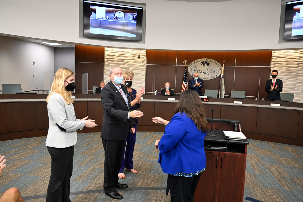 Palm Coast Mayor David Alfin immediately after his swearing in, acknowledging City Clerk Virginia Smith, with his daughter Melanie and his wife Tammy at his side, and the council he was about to join behind him--with some on the dais more enthusiastic than others about his accession. (© FlaglerLive)