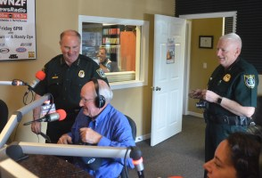 County Commissioner Dave Sullivan being arrested this morning near the end of Free For All Friday as it aired on WNZF, with Sheriff Rick Staly serving the warrant and reading it on the air, Chief Mark Strobridge preparing to handcuff the commissioner, and Relay For Life's Judy Mazzella in the lower right corner. Click on the image for larger view. (© FlaglerLive),