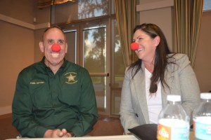 Yes, they all put on the red noses, to end the evening 'on a positive,' in Colleen Conklin's words. Above, the Flagler County Sheriff's Chief Paul Bovino and Palm Coast Mayor Milissa Holland, who not long before had told the wrenching story of her mother's suicide. Click on the image for larger view. (© FlaglerLive)