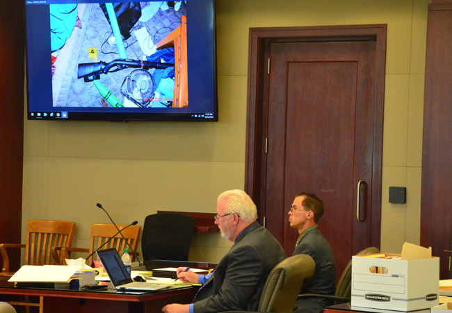Jonathan Canales, right, with his attorney, Garry Wood, and an image of the .22 rifle he is accused of using to shoot Tiffany Norman in their Mondex trailer four years ago. Canales said he'd have used a more powerful weapon if he wanted to kill her. (© FlaglerLive)
