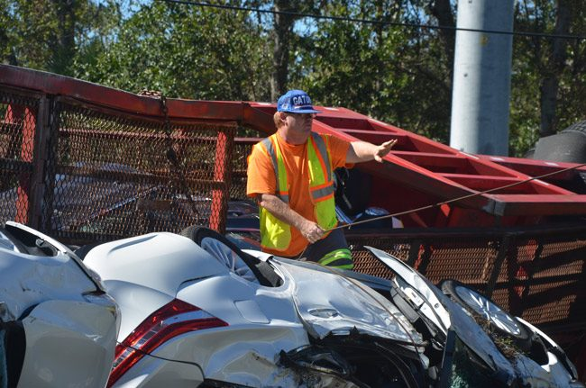John Rogers is a two-term Bunnell city commissioner, but his day job can get more interesting: he owns John's Towing in Bunnell, and often finds himself untangling wrecks, as he did Saturday, after a car transport overturned on Old Kings Road. (© FlaglerLive)
