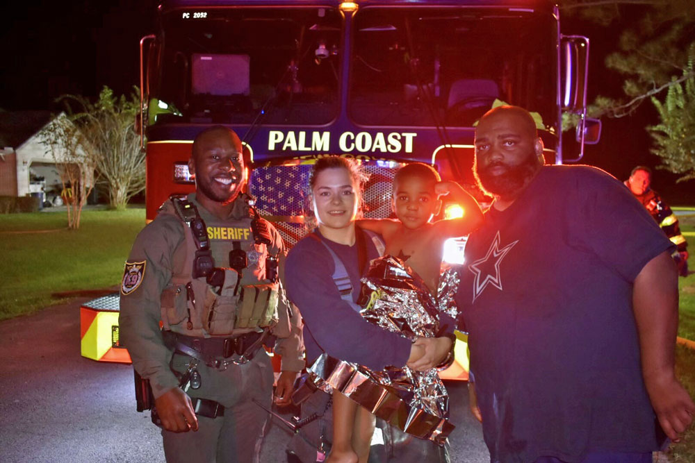 From left, Flagler County Sheriff's Deputy Marcus Dawson, Palm Coast Fire Department Firefighter-Paramedic Kalin Graham, the 3-year-old boy, and his father, Kevin Farris. (FCSO)