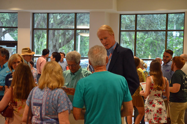Dennis McDonald, usually the tallest man in the room, speaking to a constituent at an event for political candidates earlier this summer. (© FlaglerLive)