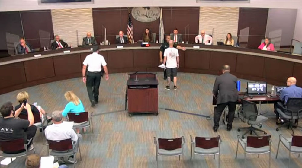 Mark Philips, in the white shirt to the right, is blocked by Sheriff's Cmdr. Phil Reynolds after Philips got in mayor Milissa Holland's face during this evening's council meeting. (© FlaglerLive via Palm Coast YouTube)