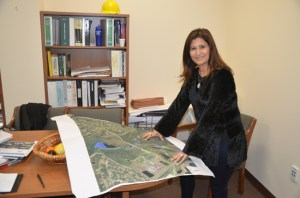 The hard hat at the top of the bookshelf is not just for show: Flagler County Engineer and Public Works Director Faith Alkhatib maps out innumerable local infrastructure projects without which the county could not function. (© FlaglerLive)