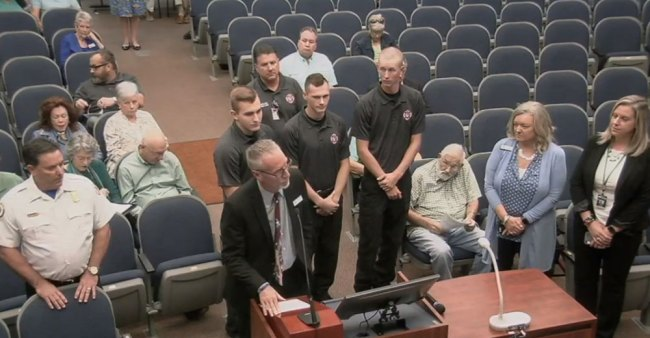 Superintendent Jim Tager, at the mic, and Fire Chief Don Petito, left, introduce Flagler County Fire Rescue's newest recruits this morning, and the first to be hired directly out of Flagler Palm Coast High School's three-year-old fire academy. The recruits are, from left, Noah Dunaway, Dylan Cronk and Beau Kruithoff, all 18. (© FlaglerLive via FCTV)