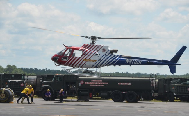 Flagler County's Fire Flight emergency helicopter during a demonstration of a 'hot refueling' maneuver with Kimble's Aviation Logistical Services at the airport last week, when an aircraft is refueled without turning off engines. The maneuver is intricate but used during critical emergency operations in the aftermath of disasters. (© FlaglerLive)