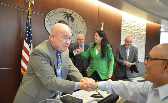 Newly-minted Palm Coast Council member Jack Howell, in the foreground, is congratulated by a supporter as Mayor Milissa Holland fist-bumps fellow-councilman and now-Vice Mayor Nick Klufas (behind Howell), with Councilman Bob Cuff and, to the right, Eddie Branquinho, who was also sworn-in today. (© FlaglerLive)