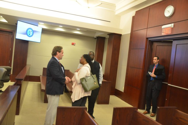 Attorney Josh Davis speaking with Kimberly Lee after the sentencing. Assistant State Attorney Jason Lewis is by the door. Lee's husband is just behind her. (© FlaglerLive)