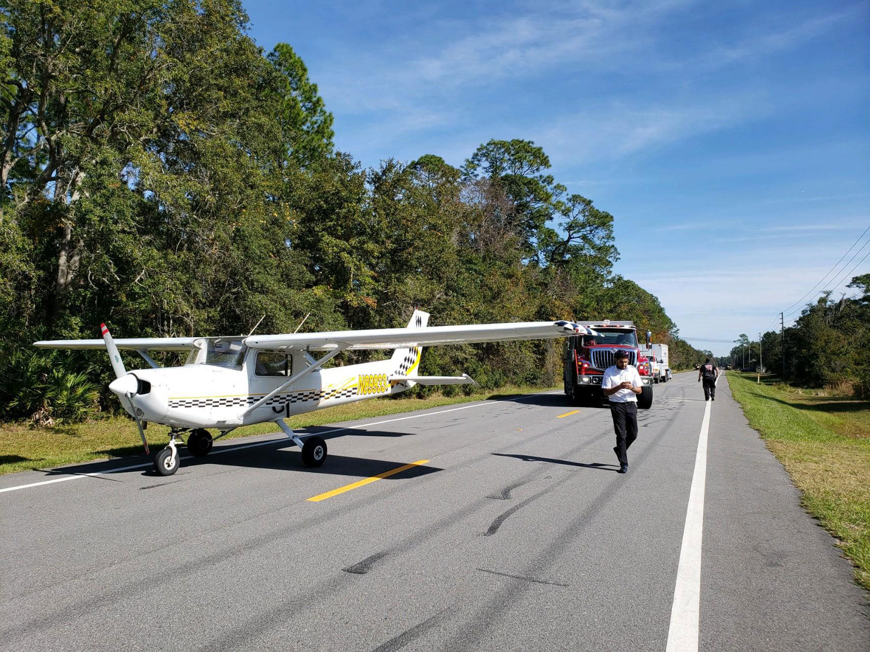 Abdullah Khawja after making the emergency landing on County Road 205 this afternoon. The power lines he swooped under are visible in the background. (Flagler County Professional Firefighters)