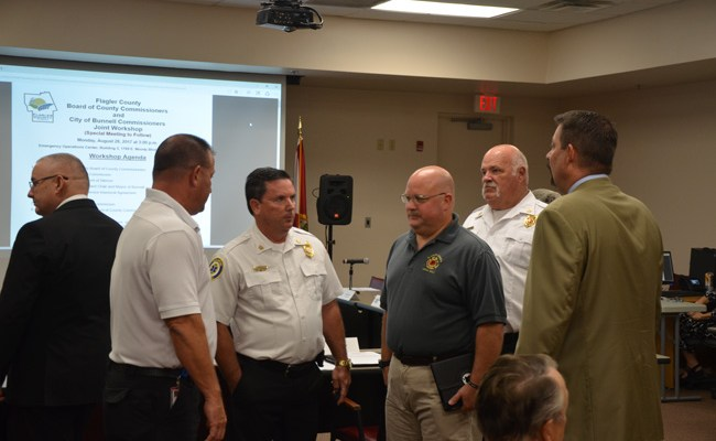 The principals in the proposed transfer of the Bunnell Fire Department to Flagler County's jurisdiction. From left, with his back to the camera, Bunnell City Commissioner John Sowell, Flagler County Fire Rescue's Joe King, Fire Chief Don Petito, Firefighters' union chief Stephen Palmer, Bunnell Fire Chief Ron Bolser, and County Administrator Craig Coffey. (c FlaglerLive)