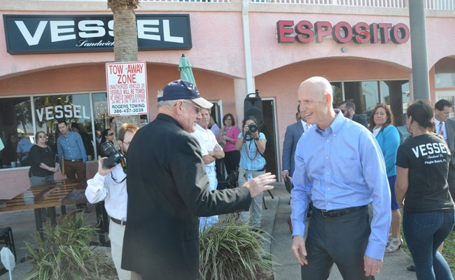 Gov. Rick Scott, right, during his last visit to Flagler County, when he was campaigning in favor of a $100 million budget for Visit Florida. He is seen here speaking with County Commissioner Dave Sullivan in Flagler Beach. (© FlaglerLive)