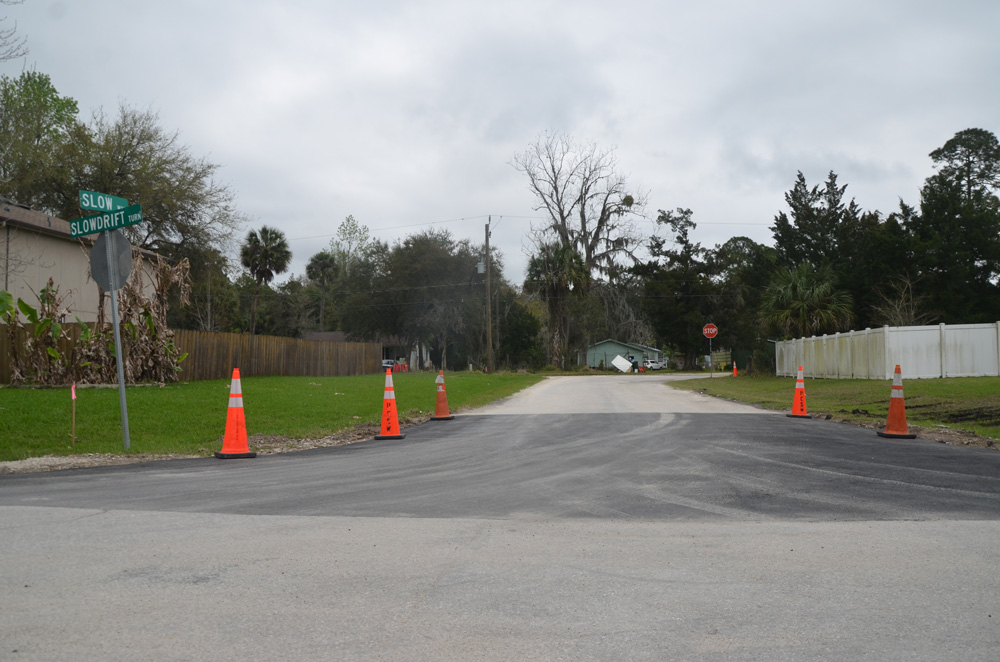 Ironically, the city is repairing Slow Turn even as it is considering closing it permanently. The Palm Coast City Council on Tuesday opted to delay the decision. Above, Slow Turn, at the intersection with Slowdrift Lane, as it looked this afternoon. (© FlaglerLive)