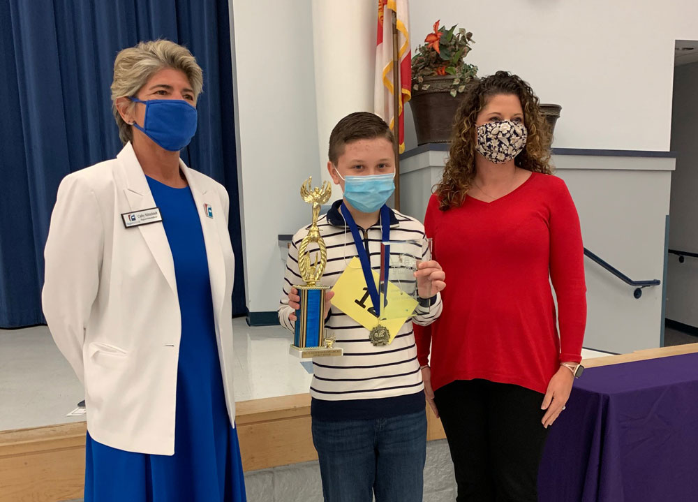 Spelling Bee winner Daniel Belkin of Indian Trails Middle School with Superintendent Cathy Mittelstadt, left, and Insian Trails Assistant Principal Amy Neuenfeldt. (Flagler Schools)