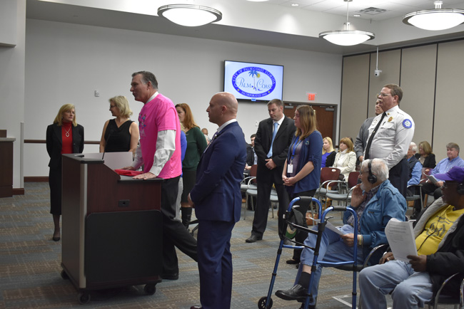 Florida Hospital Flagler's John Subers, center, in the pink shirt, presenting the $14,448 check raised by this year's Pink Army run for breast cancer awareness and treatment locally. The presentation was before the Palm Coast City Council this morning. (Palm Coast)