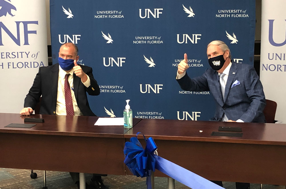 DSC President Tom LoBasso, left, and UNF President David Szymanski an official Memorandum of Understanding between the two institutions at the Oct. 6 press conference. The schools hope their collaboration that will further elevate healthcare education and support the specific needs of the region. (© FlaglerLive)