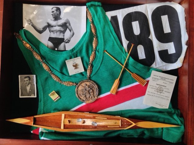 Display of Olympian Andras Toro's 1960 Olympic memorabilia from Rome 1960, inlcuding a bronze medal for canoe, his uniform and number, and a wooden model of a canoe.