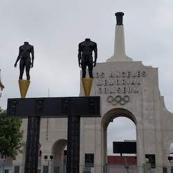Outside of the Los Angeles Memorial Coliseum, featuring statues, the Olympic rings and the Olympic cauldron.