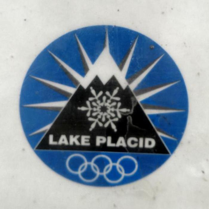 Lake Placid, New York logo with a mountain, snowflake and Olympic rings.