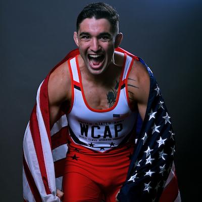 SPC Alejandro Sancho, Greco-Roman wrestler with the flag around him. Photo courtesy of U.S. Army World Class Athlete Program.