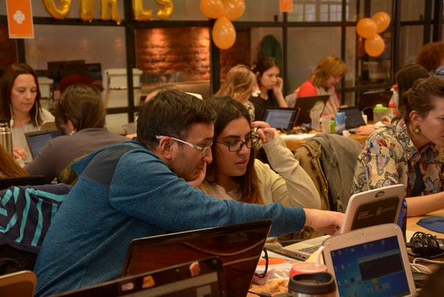 Image of adults looking at laptps in a busy coffeeshop