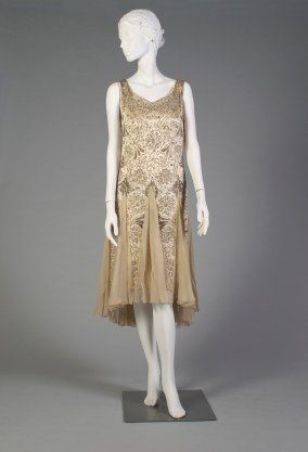 American, ca. 1925-1928. Cream silk satin, crystal and silver bugle beads in a floral pattern, inset chiffon at center back with bow trim.