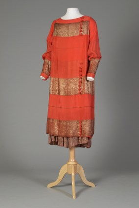 American, ca. 1926-1927. Orange silk brocaded with silver, high neck, long sleeves, bands, asymmetrical slash. Slip with a skirt of pleated lamé.