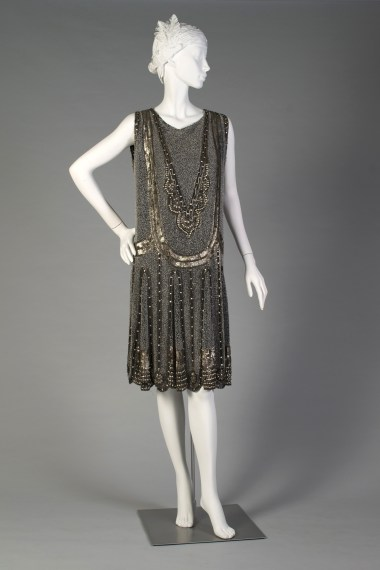 English, ca. 1925. Black chiffon sleeveless dress with all-over design of white beads, silver sequins and silver glass beads.