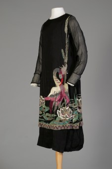 French, ca. 1927. Black silky sheath gathered at the hips with black chiffon sleeves. A large beaded crane on the front with a lotus design continuing to the back.