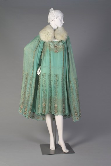 American, Peggy Hoyt, ca. 1921. Aquamarine silk, chiffon, Luneville embroidery in gold and silver beads, copper thread. Deep stand collar of fox fur.