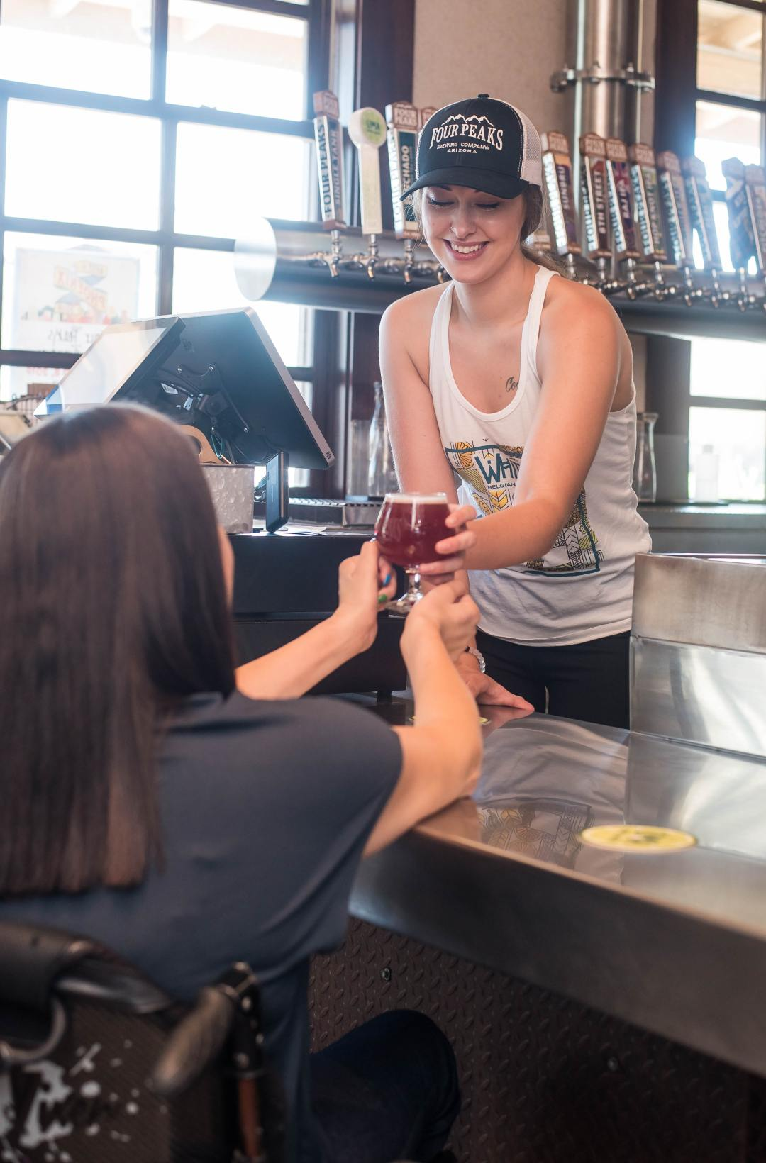 A young lady passing a beer over the counter to a lady in a wheelchair.