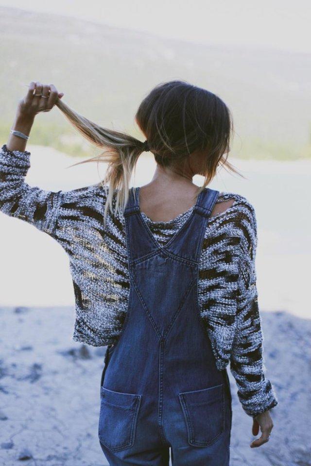 salopette en jean, pull gris et noir, cheveux attachés, bagues en or